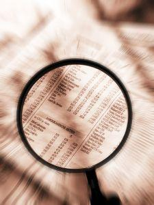 Magnifying glass examining stock pages
