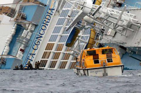 The cruise ship Costa Concordia lays on its side off the tiny Tuscan island of Giglio, Italy, Wednesday, Jan. 18, 2012. Italian searchers suspended operations on Wednesday after an enormous cruise ship grounded and partially submerged off the coast of Tuscany shifted slightly, creating concerns for the safety of divers and firefighters scouring the cruiseline for more than 20 passengers and crew still missing. (AP Photo/Andrea Sinibaldi, Lapresse) Photo: Andrea Sinibaldi / PRESL