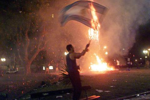 A man waves an Argentine flag at the Plaza de Mayo in Buenos Aires on Dec. 20, 2001, after police used tear gas to disperse demonstrators.